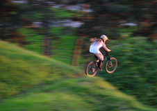 Mountain jump. Young man jump with mountain bike across the edge Royalty Free Stock Images