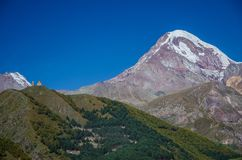 Mountain Kazbek with white snow covered peak and Gergeti Trinity church in the foreground with blue sky above