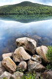 Mountain lake. A stack of rocks on the shore of a still clear mountain lake stock photography