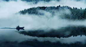 Mountain lake. Quiet mountain lake in a thick fog. In the background a mountain forest. Floats on the water in the boat people. The blue tone Stock Photo