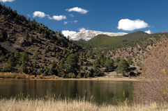 Mountain Lake. A lake reflects the pine trees on the mountain with a snow capped peak in the distance Royalty Free Stock Photos