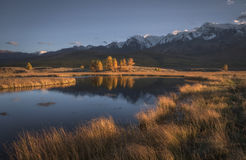 Mountain lake on a background of autumn landscape and snow capped mountains stock image