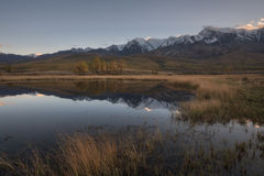 Mountain lake on a background of autumn landscape and snow capped mountains royalty free stock image