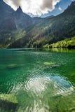 Mountain lake on the background of rocky mountains Stock Photos