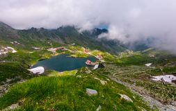 Mountain lake Balea view through the clouds. Amazing summer landscape of one of the most visited landmarks in Romanian Fagarasan mountains Stock Images