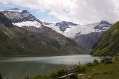 Mountain lake with benches. Mountain with glacier in Background Royalty Free Stock Photography