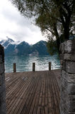 Mountain lake, boat bridge and Swiss Alps Royalty Free Stock Photos