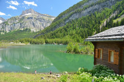 Mountain Lake and Cabin. Log cabin with a stunning  view over a mountain lake with walking girls by the waterside Royalty Free Stock Images