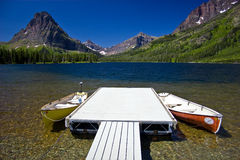 Mountain lake with canoes and dock. Canoes at dock in a glacier fed clear Rocky Mountain lake stock photography