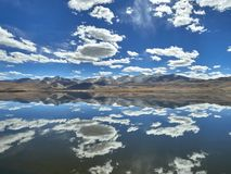 Mountain lake, chain of mountains in the background, in the blue sky white clouds, completely symmetrical mirror reflection in the Stock Photos