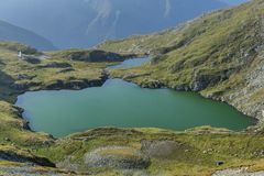 Mountain lake with crystal clear water of emerald color. Landscape from Capra Lake in Romania and Fagaras mountains in the summer. Royalty Free Stock Photo