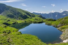 Mountain lake with crystal clear water of emerald color. Landscape from Capra Lake in Romania and Fagaras mountains in the summer. Royalty Free Stock Image