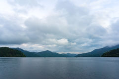 Mountain lake on dusk with fishing boats in the distance royalty free stock photography