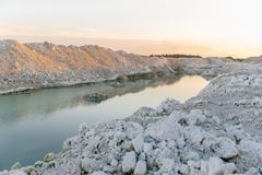 Mountain lake with emerald water at sunset. Chalky quarries - emerald blue water, vanilla sunset, white stones, pink sunset stock photo