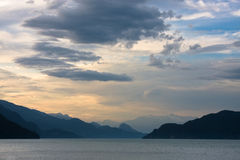 Mountain lake in the evening. Clouds drift over Harrison lake (Canada) at sundown giving a desolate atmosphere Stock Photography