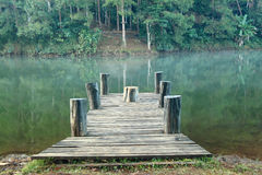 Mountain lake and flowing river with a wooden bridge Royalty Free Stock Photography