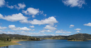 Blue calm deep water lake with gently sloping banks surrounded by hills with trees under a blue sky with small soft white clouds. Great Dividing Range, New Royalty Free Stock Photography