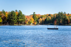 Mountain Lake with Forested Shores in the Adirondacks and Blue Sky. Mountain Lake with Forested Shores in the Adirondacks in Autumn. A Floating Platform with a Royalty Free Stock Photo