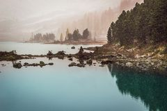 Mountain lake frosty morning. The snow on the lake shore in the rocks stock photography
