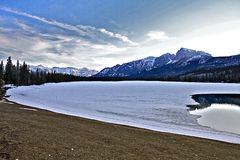 Mountain Lake and Ice. Mountain lake partially covered in ice in the spring. Blue sky, early morning light. Calm and peaceful serene setting stock images