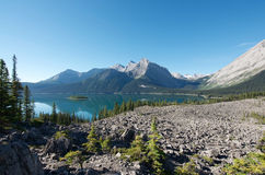 Mountain Lake with island and trees. The Upper Kananaskis Lake is a lake that has been turned into a reservoir in Kananaskis Country in Alberta, Canada.  It is Stock Photo