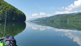 Mountain lake kayak fishing trip. A very calm kayaking trip on a mountain lake with nice water reflection of mountains on a clear summer day Stock Images