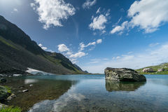 Mountain lake with large boulder and a rest stop on a mountain pass road near Davos in the Swiss Alps Stock Photography
