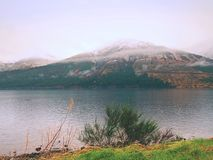 Mountain lake before misty sunset in Higland in Scotland. Snowy cone of mountain above mirroring water Stock Images