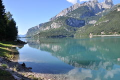 Mountain Lake Molveno, Italy. Molveno is located in Italy, Europe.  Images shows  Molveno Lake in the front, silent water with small waves in the middle and Royalty Free Stock Photos
