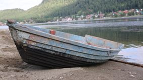 Old boat on the lake. Mountain lake, old blue boat on a sand beach, npeeling paint stock footage