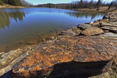 Mountain lake, old rocks and deep blue sky Royalty Free Stock Images