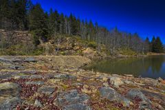 Mountain lake, old rocks and deep blue sky Royalty Free Stock Photos
