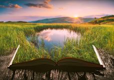Mountain lake on the pages of an open book. The small mountain lake in a grass at sunset on the pages of an open magical book. Majestic landscape. Nature and stock photo