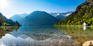 Mountain lake panorama with mountains and reflection in the lake. In the morning Royalty Free Stock Photography
