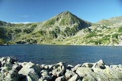 Mountain lake and peak. Bucura Lake the largest romanian  mountain lake and Custura Bucurei Peak Royalty Free Stock Images