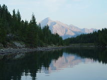 Mountain lake reflection at sunset. Dusk in the mountains, summits, forest, and Stock Photos