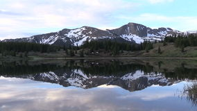 Mountain Lake Reflection Zoom in. A zoom in on a scenic sunrise reflected in a Colorado mountain lake stock footage