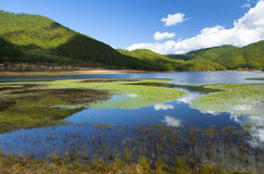 Mountain Lake Reflections. Bright clouds reflect in the still waters of a mountain lake in Yunnan Province, China Stock Images