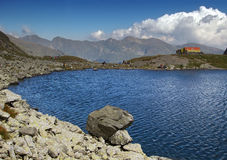 Mountain lake with rescue point. Mountain lake Caltun with red cross rescue point on the shore peaks in background in Fagaras range in Transylvania Romania Royalty Free Stock Photography