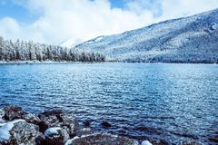 Mountain lake with rocks on the shore, winter fog over the water surface. Travel to the mountains on foot, wildlife Stock Photography