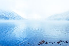 Mountain lake with rocks on the shore, winter fog over the water surface. Travel to the mountains on foot, wildlife Royalty Free Stock Image
