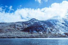 Mountain lake with rocks on the shore, winter fog over the water surface. Travel to the mountains on foot, wildlife Stock Image