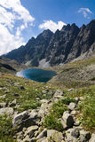 Mountain lake and rocky ridge under the blue sky Stock Photography
