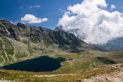Mountain lake and rocky ridge under the blue sky Royalty Free Stock Photo