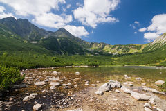 Mountain lake and rocky ridge under the blue sky Stock Images