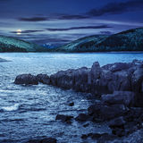Mountain lake with rocky shore at night Stock Photo
