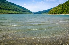 Mountain lake shore with waves in foreground, cloudy sky autumn day and distant green hills at horizon in the background. Mountain lake shore with small waves in Royalty Free Stock Photography