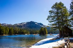 Mountain Lake Shoreline With Snow Melting In Springtime. Mountain Lake Shoreline With Cabin & Snow Melting In Springtime Stock Image
