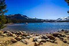 Mountain Lake Shoreline In Springtime. Shoreline With Large Boulders At Mountain Lake In Springtime With Melting Snow Stock Photo