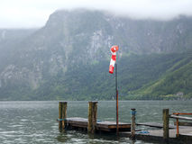 Mountain lake with small wooden jetty, pier mole, wind sleeve. Alpine massif, beautiful canyon in Austria. Royalty Free Stock Images